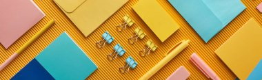 panoramic shot of colorful arranged office stationery supplies on yellow
