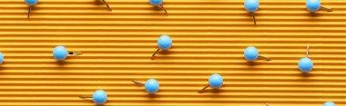 Panoramic shot of push pins on textured yellow paper stock vector