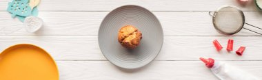 panoramic shot of delicious muffin and baking tools on wooden table