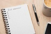 notebook s výstupním rozhovorem, psací prostor a čísla na dřevěném stole blízko smartphone, pera a šálku kávy