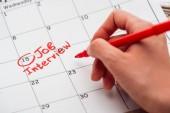 oříznutý pohled na rukopis s červenou značkou na tiskovém kalendáři s psaním rozhovoru s prací