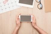 oříznutý pohled náboru přidržený smartphone s prázdnou obrazovkou na dřevěném stole