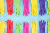 Fotografie flat lay with multicolored rubber gloves on blue background