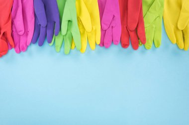 multicolored rubber gloves on blue background with copy space