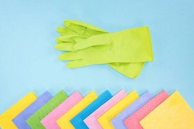 top view of green rubber gloves and multicolored rags on blue background