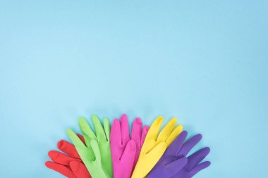 top view of multicolored rubber gloves on blue background with copy space