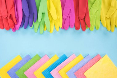 top view of multicolored bright rubber gloves and rags on blue background with copy space