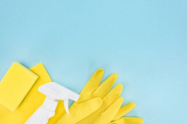 top view of yellow rubber gloves, sponge, rag and spray on blue background with copy space