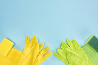 top view of yellow and green rubber gloves, sponges, rags on blue background with copy space