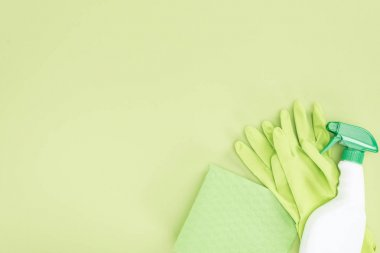 top view of green rubber gloves, rag and spray bottle on green background