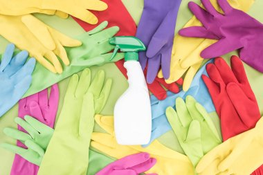 top view of messy scattered multicolored rubber gloves and white spray bottle with cleanser on green background