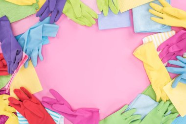 top view of messy scattered multicolored rags and rubber gloves on pink background with copy space