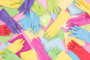 top view of messy scattered multicolored rags and rubber gloves on pink background