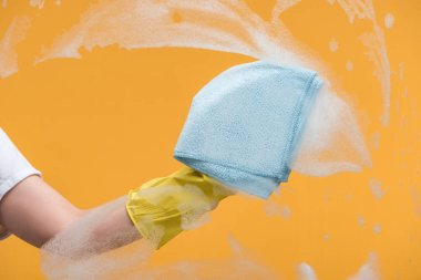 cropped view of cleaner in rubber glove cleaning glass with rag on orange background