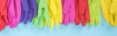 panoramic shot of bright multicolored rubber gloves on blue background