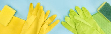 panoramic shot of yellow and green rubber gloves, sponges, rags on blue background