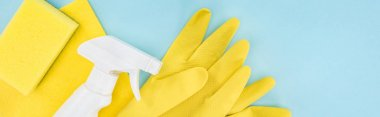 panoramic shot of yellow rubber gloves, sponge, rag and spray on blue background with copy space