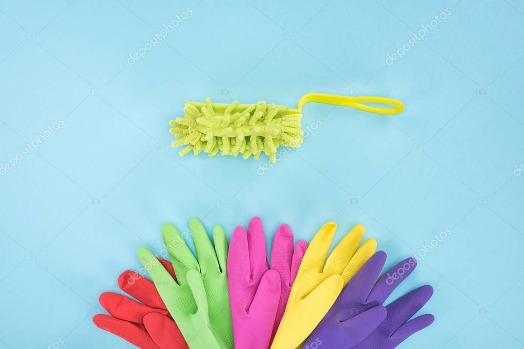 flat lay with multicolored rubber gloves and sponge on blue background