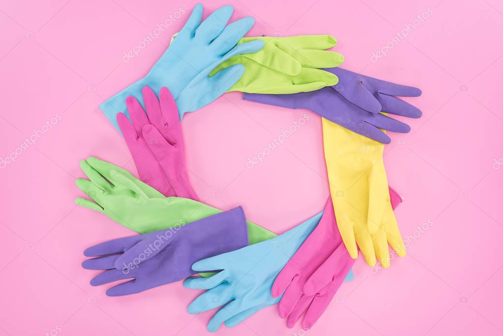 frame made of multicolored rubber gloves on pink background with copy space