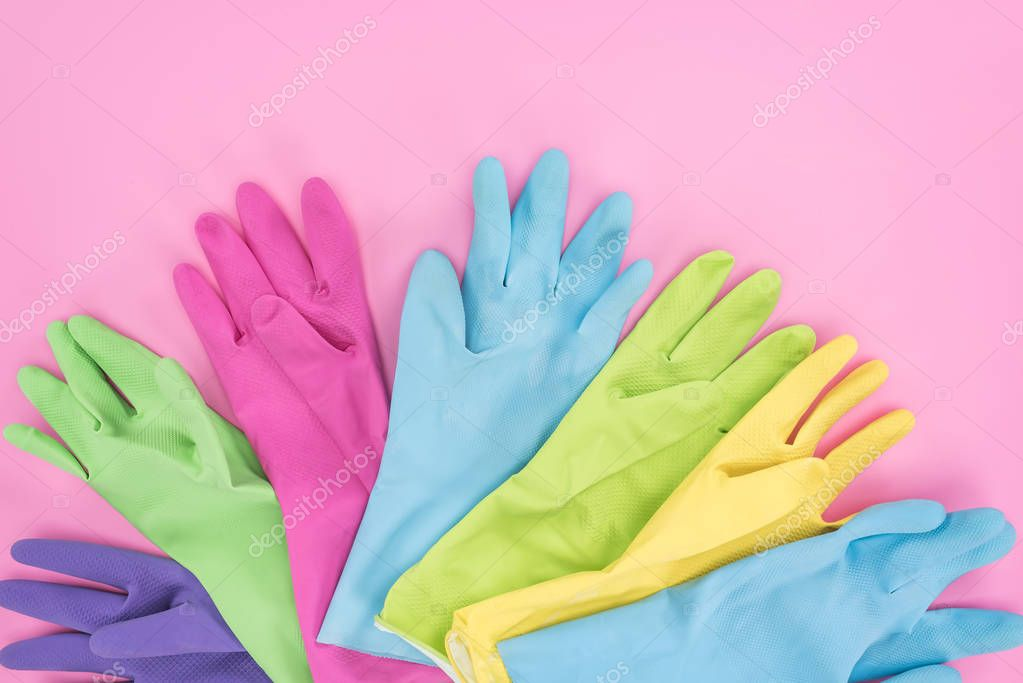top view of multicolored rubber gloves on pink background