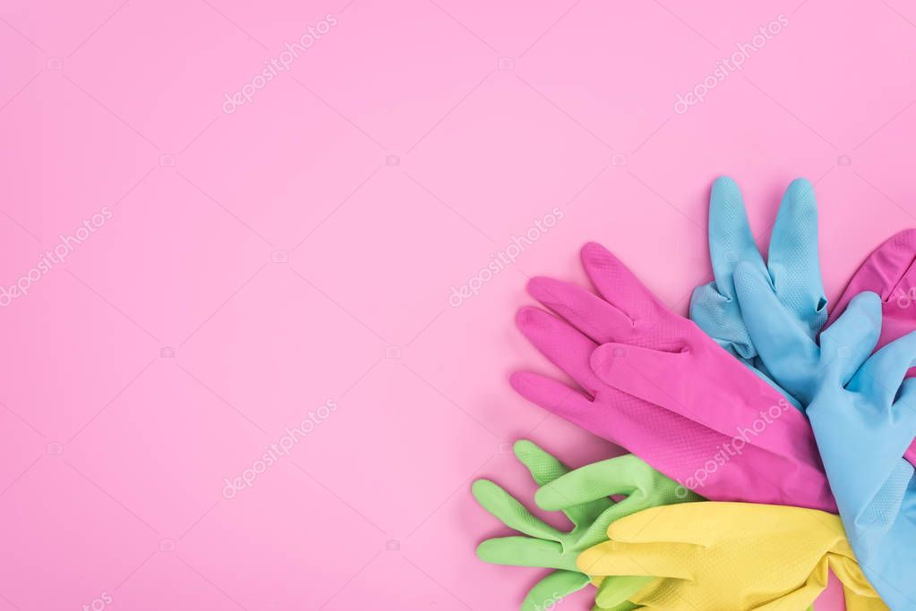 top view of multicolored rubber gloves on pink background with copy space
