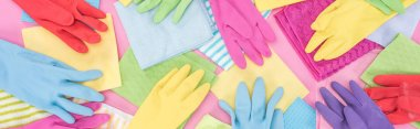 panoramic shot of scattered multicolored rags and rubber gloves on pink background