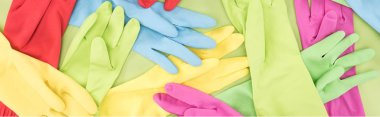 panoramic shot of scattered bright multicolored rubber gloves on green background