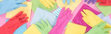 panoramic shot of scattered colorful rags and rubber gloves on pink background