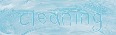 Panoramic shot of glass covered with white foam on blue background with cleaning lettering stock vector