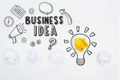horní pohled na obchodní nápad nápis v blízkosti ilustrace a zmačkané papírové kuličky na bílém pozadí, obchodní koncept