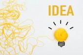 pohled shora na žlutou pletenou kouli v blízkosti žárovky a nápis nápadu na bílém pozadí, obchodní koncept