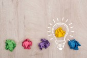 top view of multicolored crumpled paper balls and light bulb illustration on wooden surface, business concept