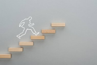 top view of drawn man running on wooden blocks symbolizing career ladder on grey background, business concept