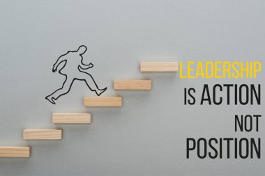 top view of drawn man running on wooden blocks symbolizing career ladder near leadership is action not position inscription on grey background, business concept