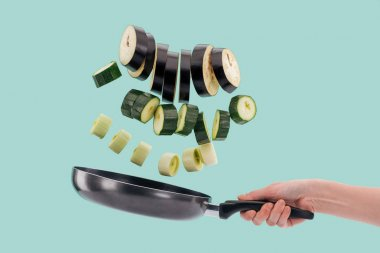 Cropped view of woman holding frying pan with sliced fresh vegetables above isolated on turquoise