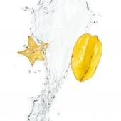 celé zralé exotické hvězdné ovoce a plátky s vodou stříkající a kapky izolované na bílém