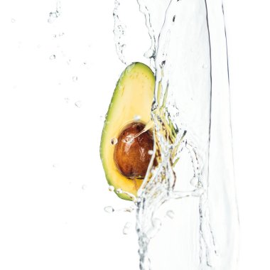 ripe nutritious avocado half with seed and water splash with drops isolated on white