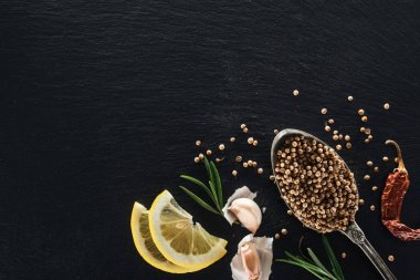 top view of coriander seeds in silver spoon on black background with dried chili pepper, lemon, herbs and garlic