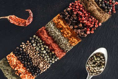 top view of traditional indian spices on textured black background near spoon with white pepper and dried chili pepper