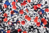 Top view of abstract silver and red confetti on blue background