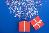 scatola regalo rossa e coriandoli lucidi multicolori su sfondo blu