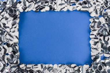 Top view of silver confetti frame on blue background stock vector