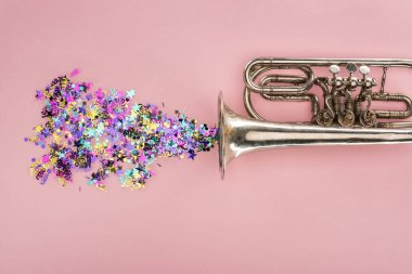 colorful confetti with trumpet on pink background