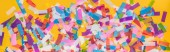 Panoramic shot of colorful confetti on yellow party background