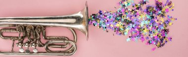 Panoramic shot of trumpet and colorful confetti on pink background