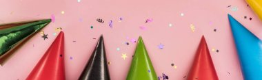 Panoramic shot of multicolored party hats on pink  festive background