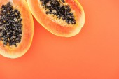 top view of ripe tropical papaya halves with black seeds isolated on orange