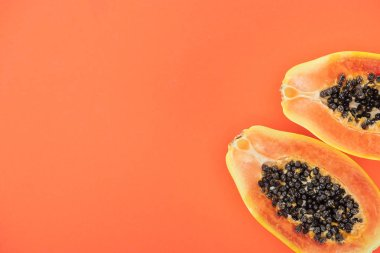 top view of ripe exotic papaya halves with black seeds isolated on orange with copy space