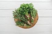 pohled na zelený petržel, Rosemary a Tyme na hnědém pahýlu na bílém dřevěném stole