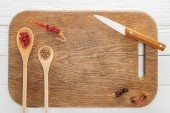 top view of knife, spoons with coriander and pink peppercorn, dried chili peppers on wooden chopping board with copy space